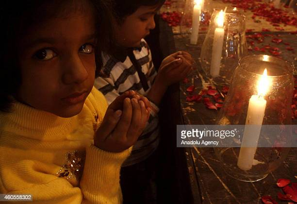 Children from Pakistani political party Muttahida Qaumi Movement pray as they attend a candle vigil in Karachi Pakistan on December 16 2014 in memory...
