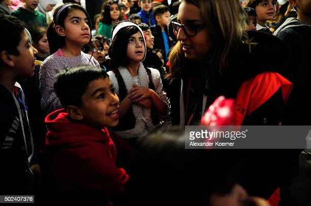 Children from Syria and Afghanistan look at a volunteer dressed as Santa Claus while greeting them at a shelter for migrants and refugees on December...