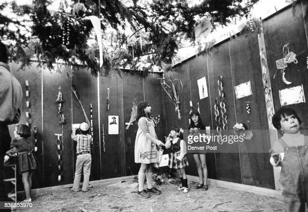 Children from Temple Rodef Shalom discuss where to hang the various succos decoration they have made Baskets posters drawings paper chains and dried...