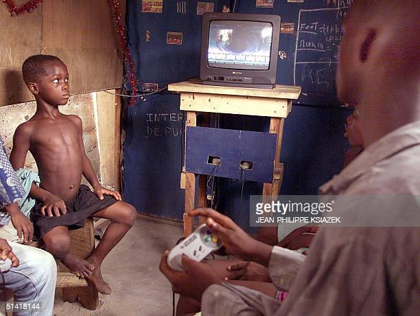 Children from the Adjame neighborhood of Abidjan are gathered in a shed 23 December to play with a Playstation game for which they have to pay 25...