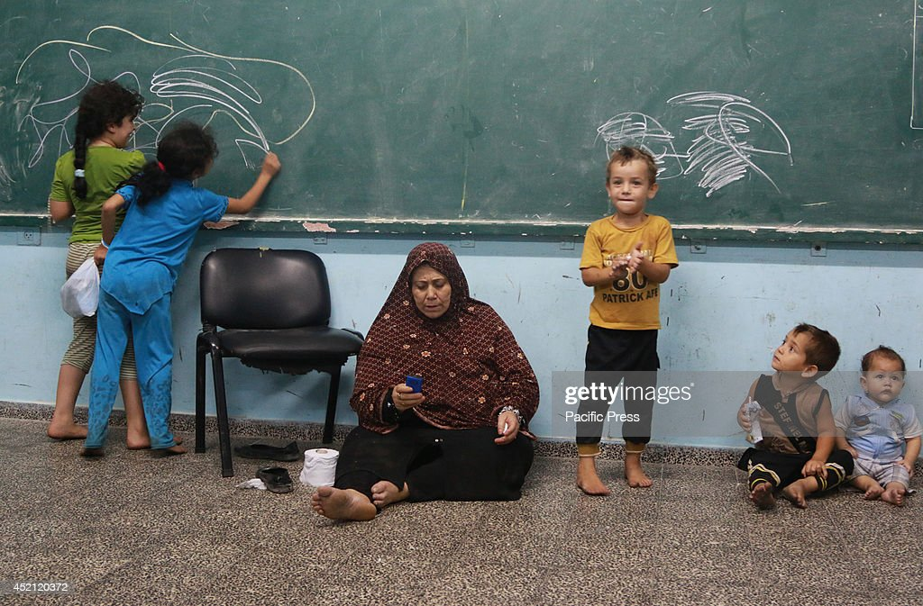 Children from the Al-Atar family playing around their grand mother in a UN school in Gaza after receiving a call from the Israeli army asking them to leave their home before an attack. They had to run away from the north of Gaza to Gaza city to the UN school looking for safe place to seek refuge.