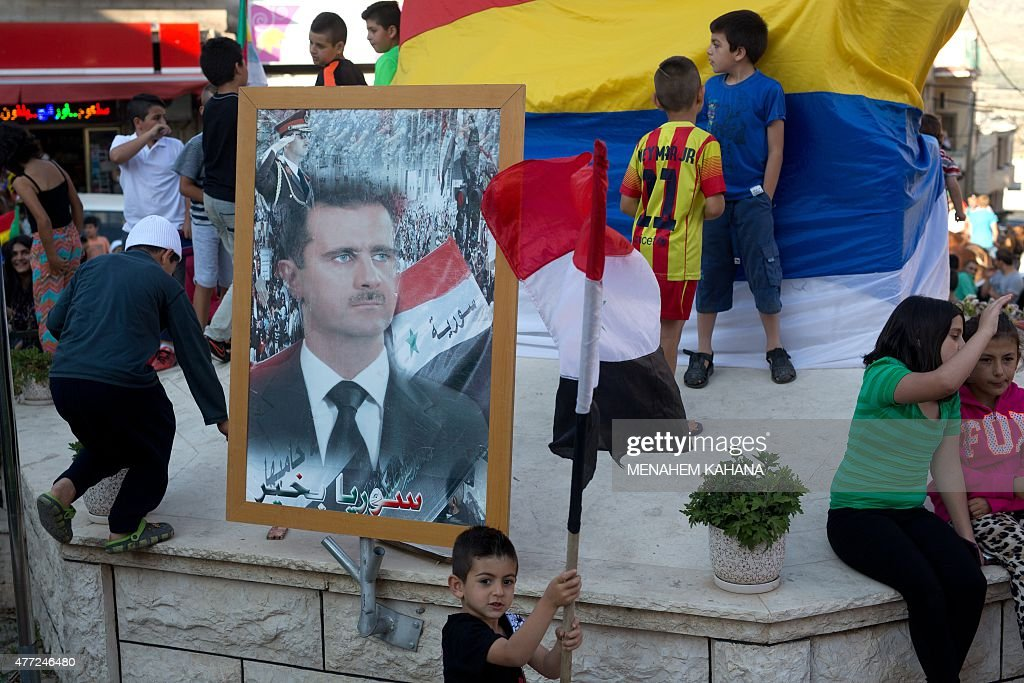 Children from the Druze community of the Israeliannexed Golan Heights play next to portrait of Syrian President Bashar alAssad during a demonstration...