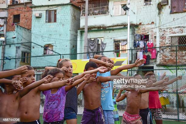 Children from the Sao Carlos Shantytown learn archery in Rio de Janeiro Brazil on September 16 2015 AFP PHOTO / CHRISTOPHE SIMON