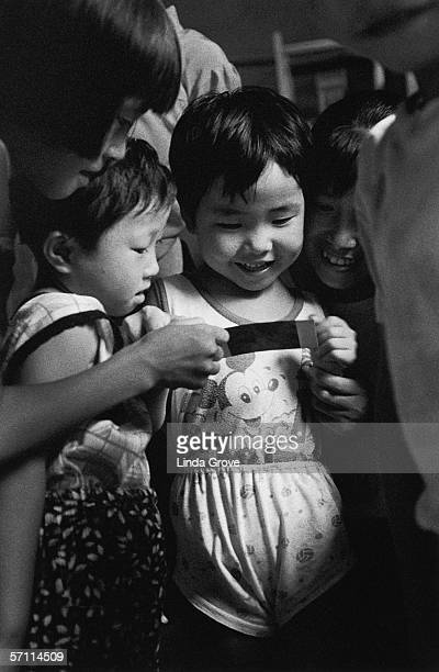 Children from the Yellow Mountain region of China are amused by a Polaroid photograph 1996 One of them is wearing a Mickey Mouse vest