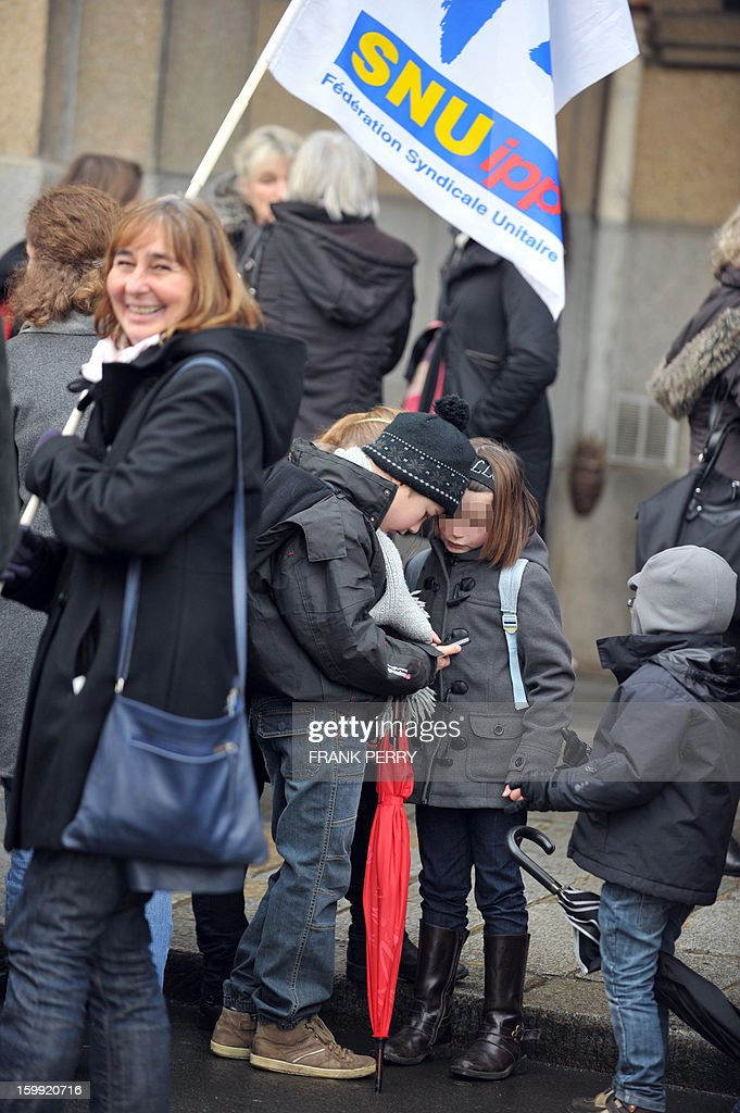 Children gather alongside adults in front of the headquarters of the local office of the Education department, on January 23, 2013, in Rennes, as they take part in a nationwide strike and protest action against a proposed reform to increase the class time of primary school students. Around 80 people gathered in Rennes as several hundred other teachers gathered at protest rallies in various cities across the country. AFP PHOTO / FRANK PERRY