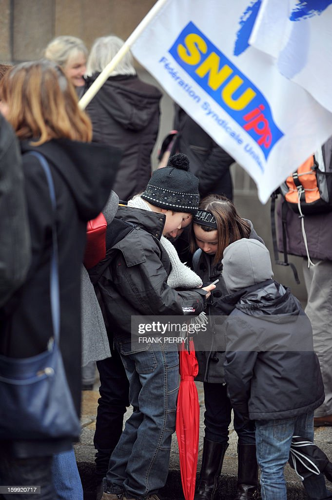 Children gather alongside adults in front of the headquarters of the local office of the Education department, on January 23, 2013, in Rennes, as they take part in a nationwide strike and protest action against a proposed reform to increase the class time of primary school students. Around 80 people gathered in Rennes as several hundred other teachers gathered at protest rallies in various cities across the country.