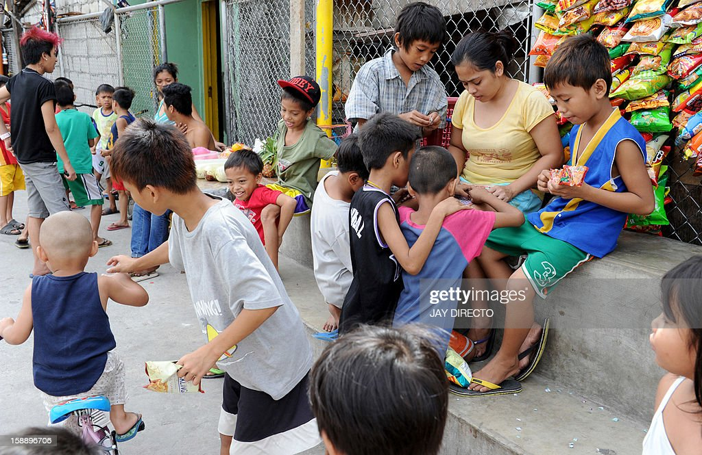 Children gather around a basketball court to play in Manila on January 3, 2013. A Catholic couple has asked the Philippines' top court to stop a historic birth control law, their lawyer said on January 3, in the first of many legal challenges church leaders have vowed against the measure. AFP PHOTO / JAY DIRECTO