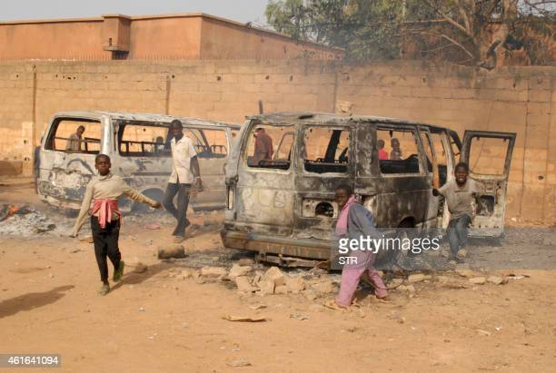 Children gather by charred vehicles that were burnt down during violent protests after thousands of protesters gathered following Friday prayers to...