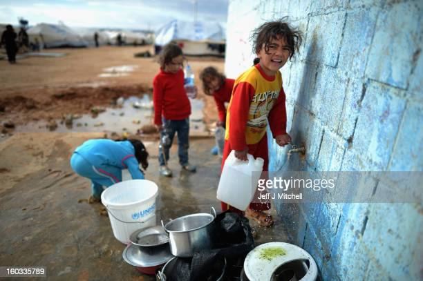Children gather water as Syrian refugees go about their daily business in the Za'atari refugee camp on January 29 2013 in Mafraq Jordan Record...