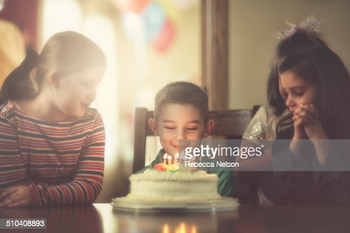 children gathered around boy with birthday cake