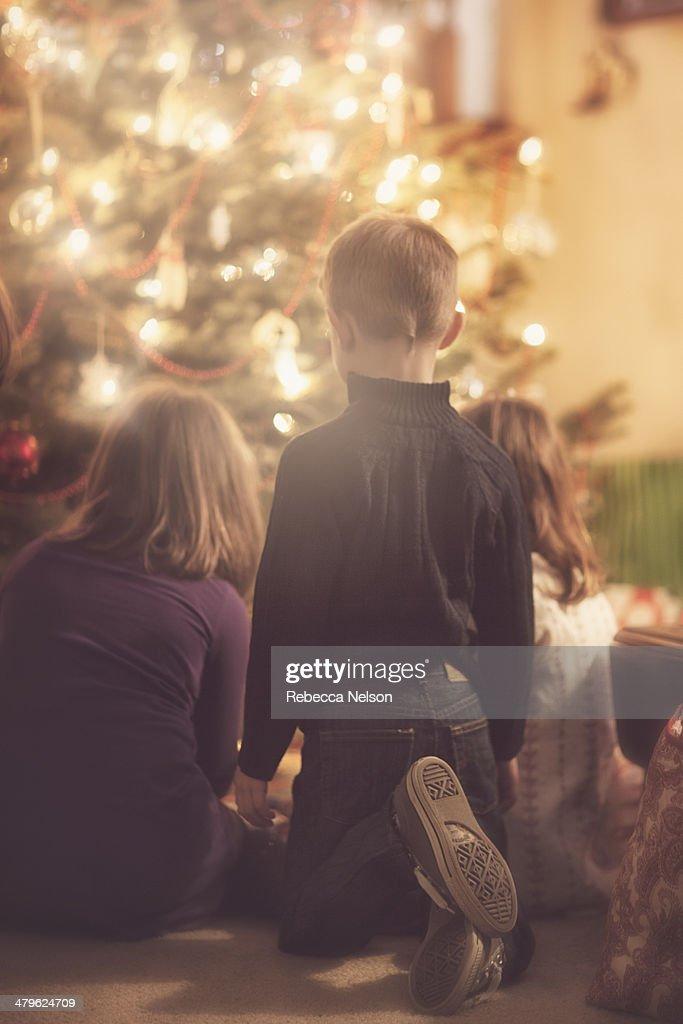 Children gathered around Christmas tree