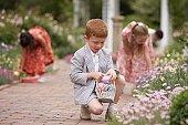 Children gathering Easter eggs in garden