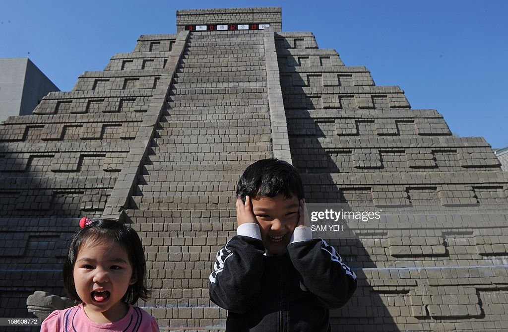 Children gesture in front of a replica of a Mayan pyramid before a count-down ceremony organized by the National Museum of Natural Science to help ensure the public it is not the end of the world, in central Taichung on December 21, 2012. A digital 'doomsday clock' on top of a two-storey replica Mayan pyramid erected at a museum in central Taiwan's Taichung city completed its countdown for the end of the world at 0600 GMT -- midnight in Mexico. AFP PHOTO / Sam Yeh