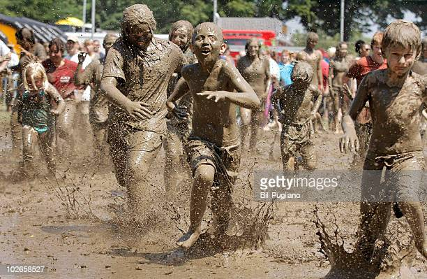 Children get some relief from the heat by playing in a gigantic lake of mud at the annual Mud Day event July 6 2010 in Westland Michigan The lake was...