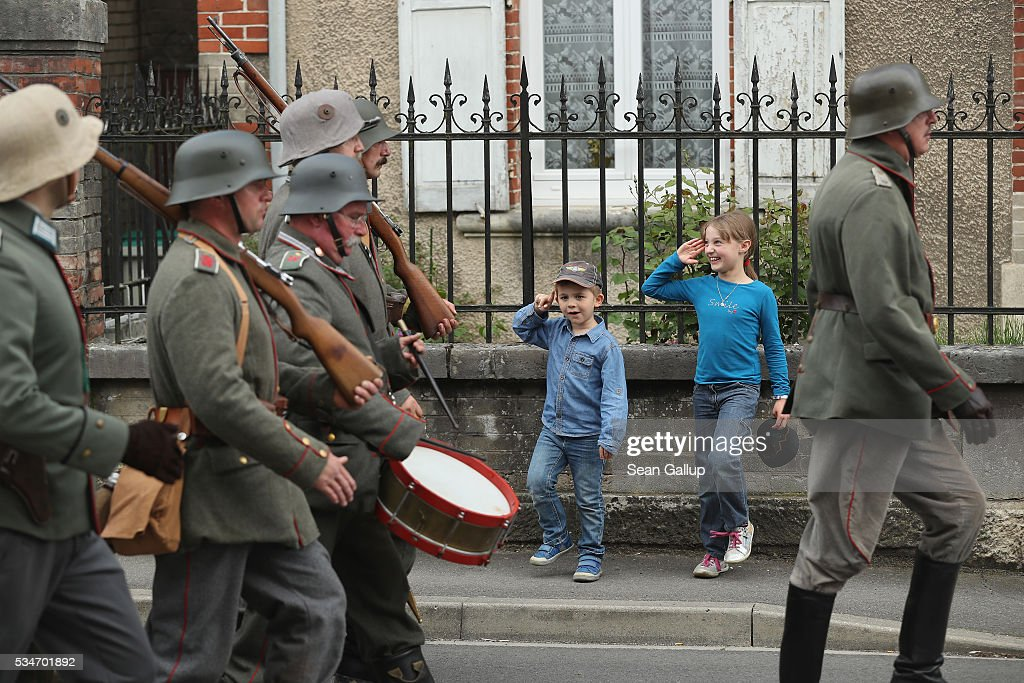 Children giggle and stand at attention as history reenactors wearing World War I German military uniforms parade past on May 27, 2016 in Verdun, France. The governments of France and Germany will commemorate the 100th anniversary of the World War I Battle of Verdun with ceremonies this coming Sunday. Approximately 300,000 soldiers lost their lives in the 10-month campaign that was among the most grueling battles of World War I.