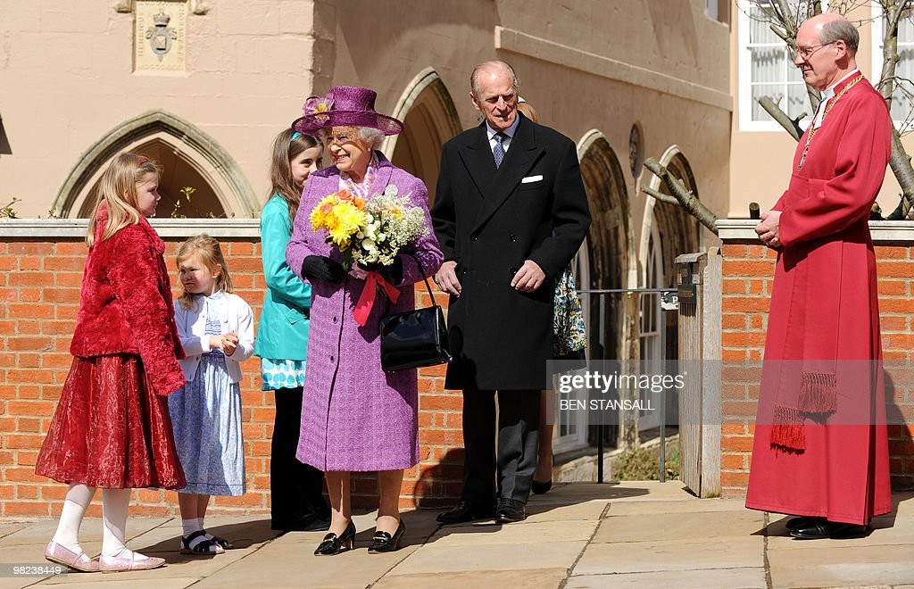 Children give flowers to Britain's Queen Elizabeth II (R) as she leaves with Prince Philip, the Duke of Edinburgh (L) an Easter Sunday church service in Windsor on April 4, 2019.