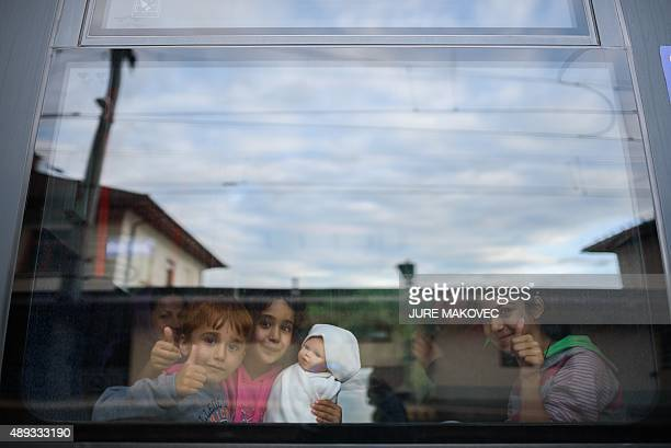 Children give the thumbs up after boarding a train to Graz at a railway station in Spielfeld on September 20 2015 Some 150 migrants entered Austria...