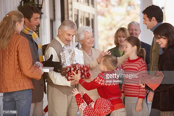 Children giving presents to their grandparents outdoors