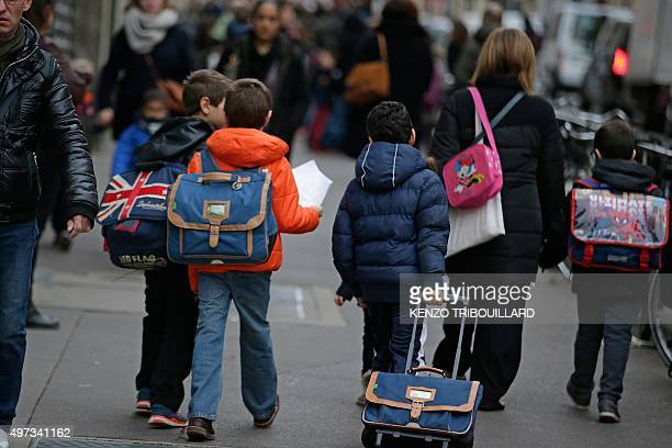 Children go to school early on November 16 2015 in Paris three days after the terrorist attacks that left over 130 dead and more than 350 injured...