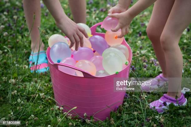 Children grabbing water balloons from a bucket