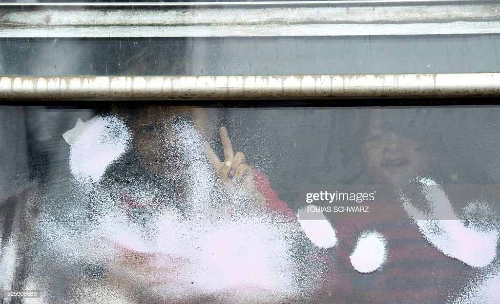 Children greet journalists from behind a window at a makeshift camp for migrants and refugees near the village of Idomeni not far from the Greek-Macedonian border on April 29, 2016. Some 54,000 people, many of them fleeing the war in Syria, have been stranded on Greek territory since the closure of the migrant route through the Balkans in February. / AFP / TOBIAS