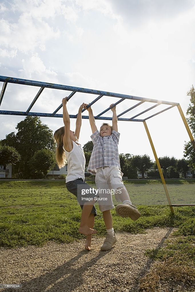 Children hanging from climbing frame