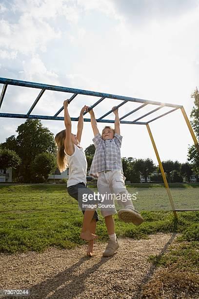 Children hanging from climbing frame