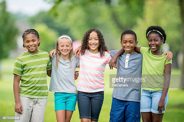 Children Happily Standing Together at the Park