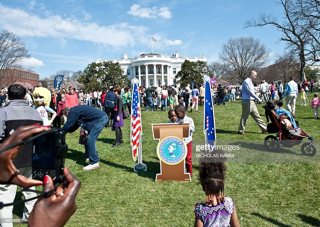 Children have their picture taken at a mock presidential rostrum during the annual White House Easter Egg Roll in Washington on April 1, 2013. AFP PHOTO/Nicholas KAMM