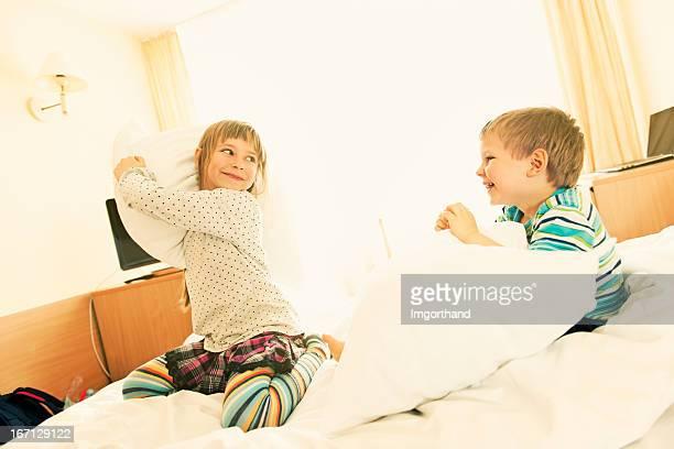 Enfants ayant une bataille d'oreillers.