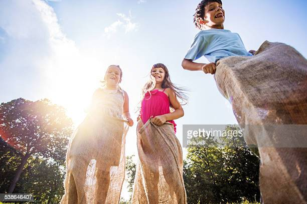 Children having a sack race outdoors.