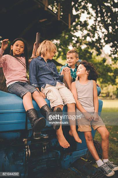 Children having fun on an old tractor together on farm