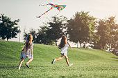 Little pretty girls having fun outdoor. Two cute girls are running on green grass with kite. Best friends.