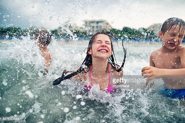 Children having fun playing and splashing in cold sea waves