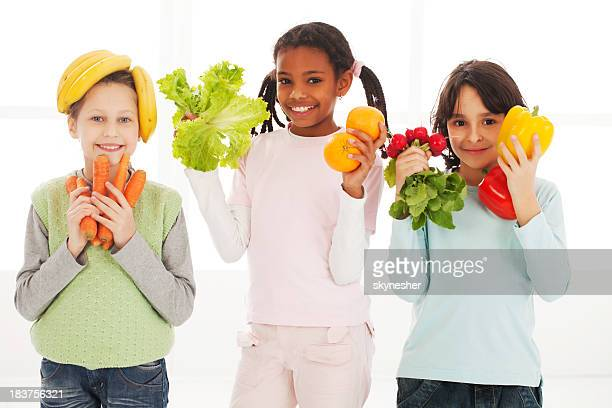 Children having fun. They hold vegetables and looking at camera.