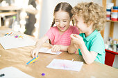 Two kids having fun at the table while drawing. They are writing letter on paper