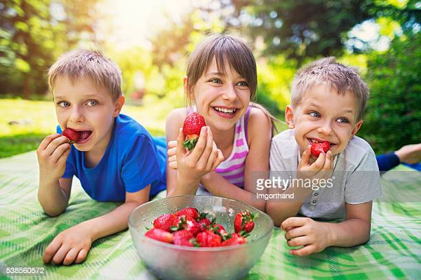 Children having picnic and eating strawberries in garden