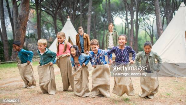 Children having sack race at campsite