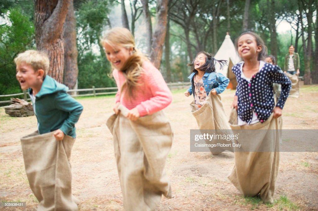 Children having sack race in field