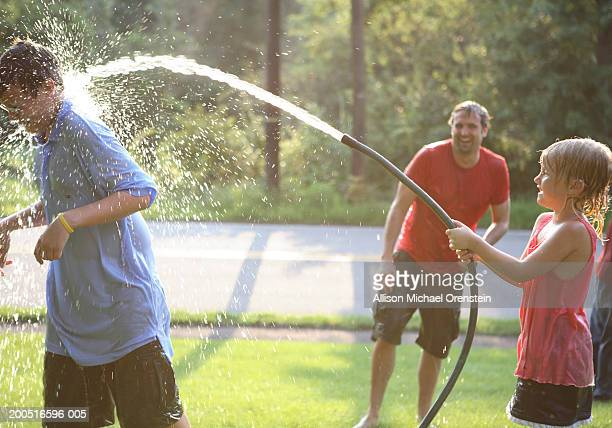 Children (4-11) having water fight with father, outdoors