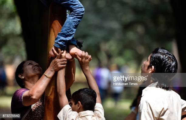 Children helping a child as he tries to climb on a Mallakhamb pole during Makkala Hanna Children Festival at Cubbon Park on November 12 2017 in...