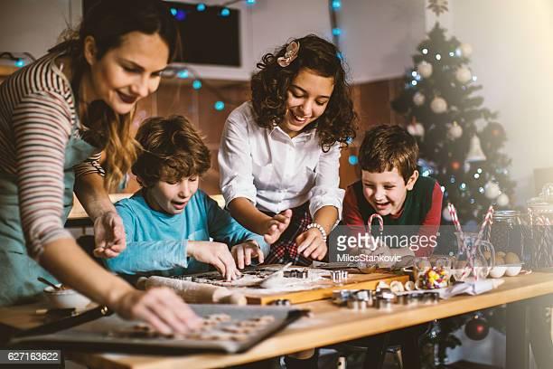 Niños hornear galletas para ayudar a la madre de víspera de Navidad