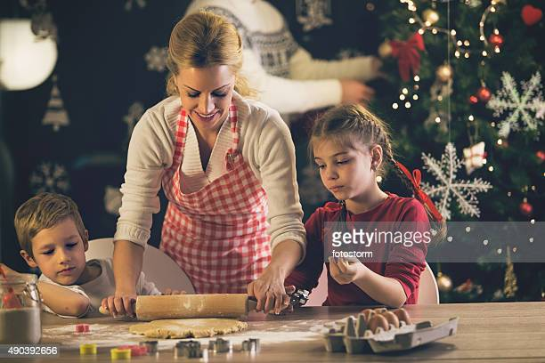 Children helping mother baking cookies for Christmas