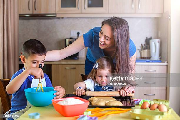 Children helping mother baking cookies