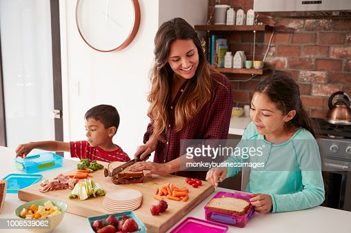 Children Helping Mother To Make School Lunches In Kitchen At Home : Stock Photo