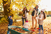 Children Helping Parents To Collect Autumn Leaves In Garden