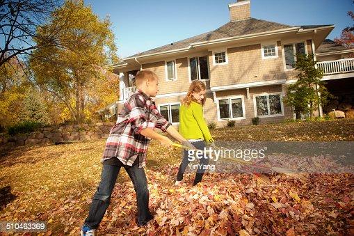 Children Helping Rake Leaves in Backyard