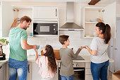 Children Helping To Put Away Crockery In Kitchen Cupboards