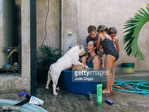 Children helping woman bathe in plastic tub