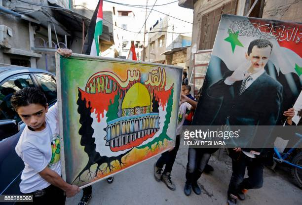Children hold a banner bearing an image of Jerusalem's Dome of the Rock next to a poster of the Syrian president during a demonstration against US...